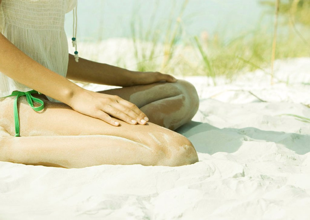 Woman sitting in sand, low section : Stock Photo