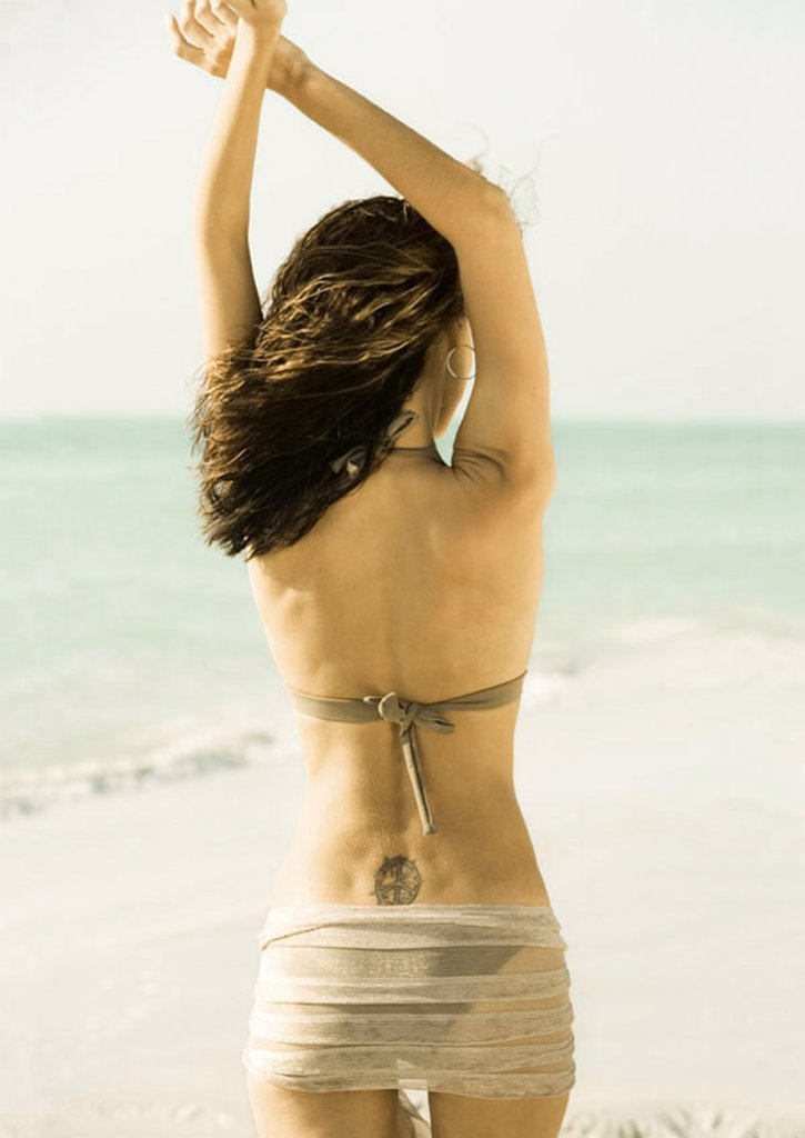 Woman standing on beach with arms up, rear view : Stock Photo