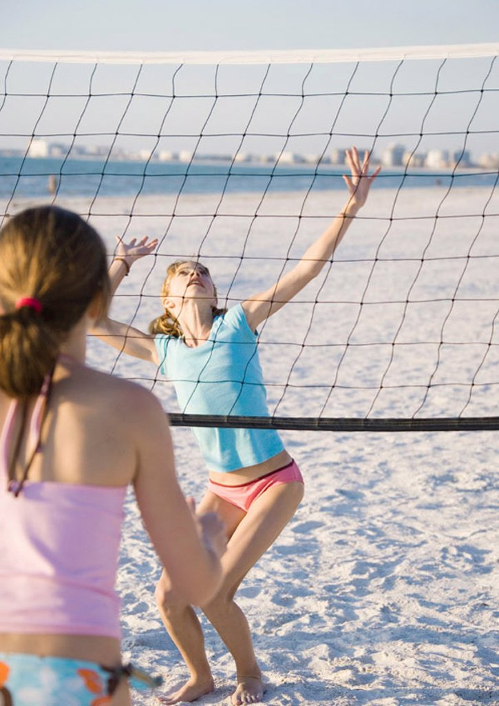 Preteen girls playing beach volleyball : Stock Photo