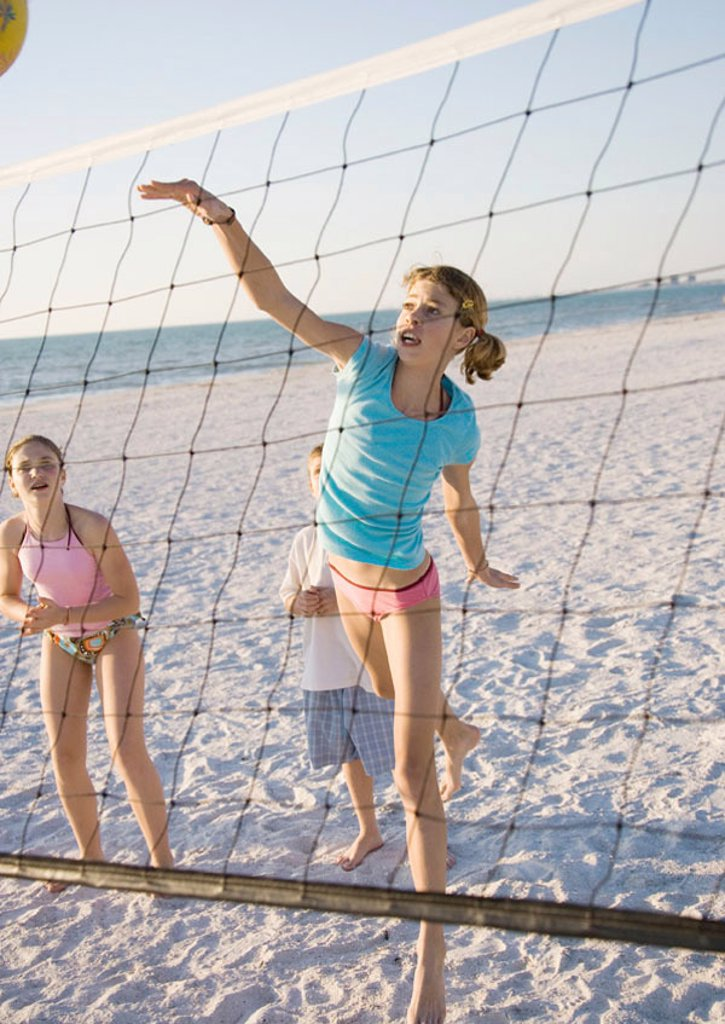 Stock Photo: 1569R-9045058 Preteen girls playing beach volleyball