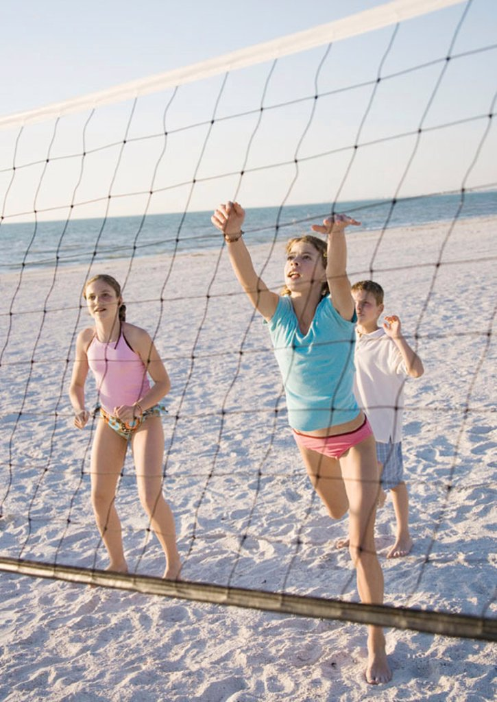Kids playing beach volleyball : Stock Photo