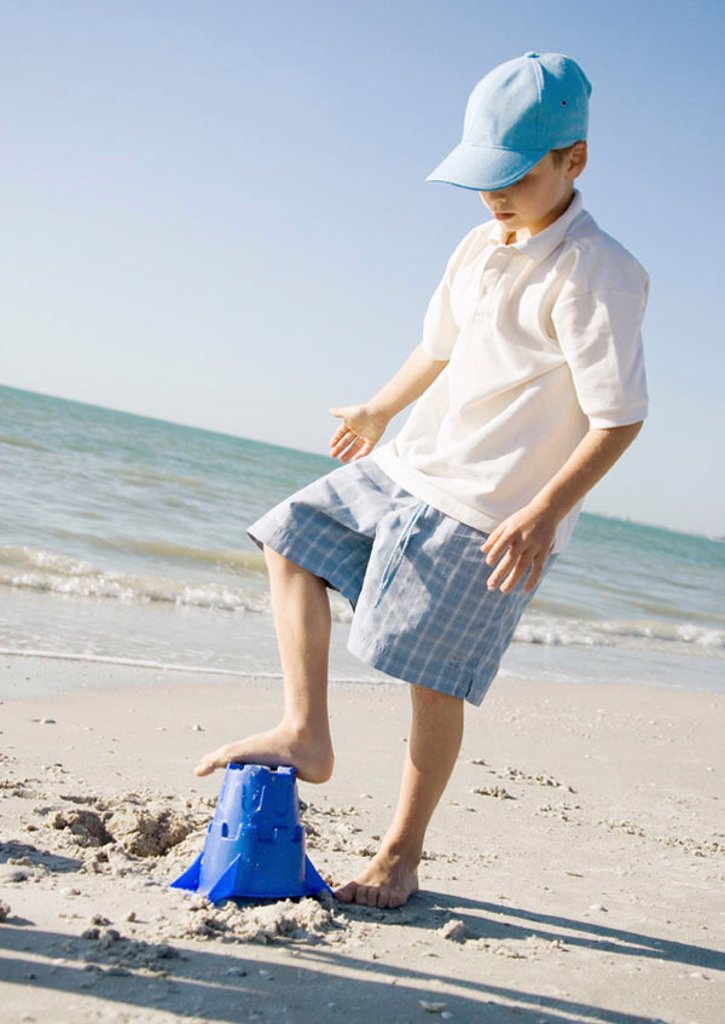 Boy stepping on sand bucket on beach : Stock Photo