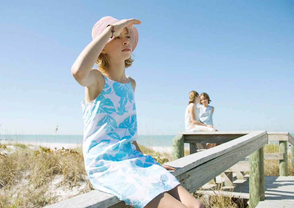Girl sitting on railing of beach walkway, shading eyes : Stock Photo