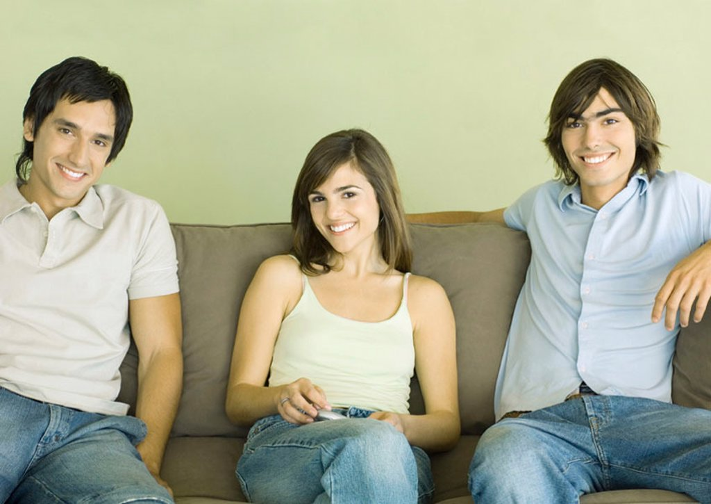 Group of young adult friends sitting on sofa : Stock Photo