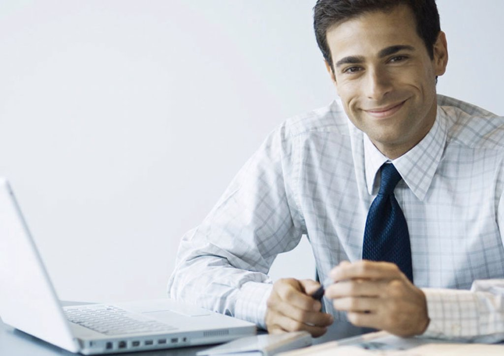 Businessman sitting at desk next to laptop, smiling at camera : Stock Photo