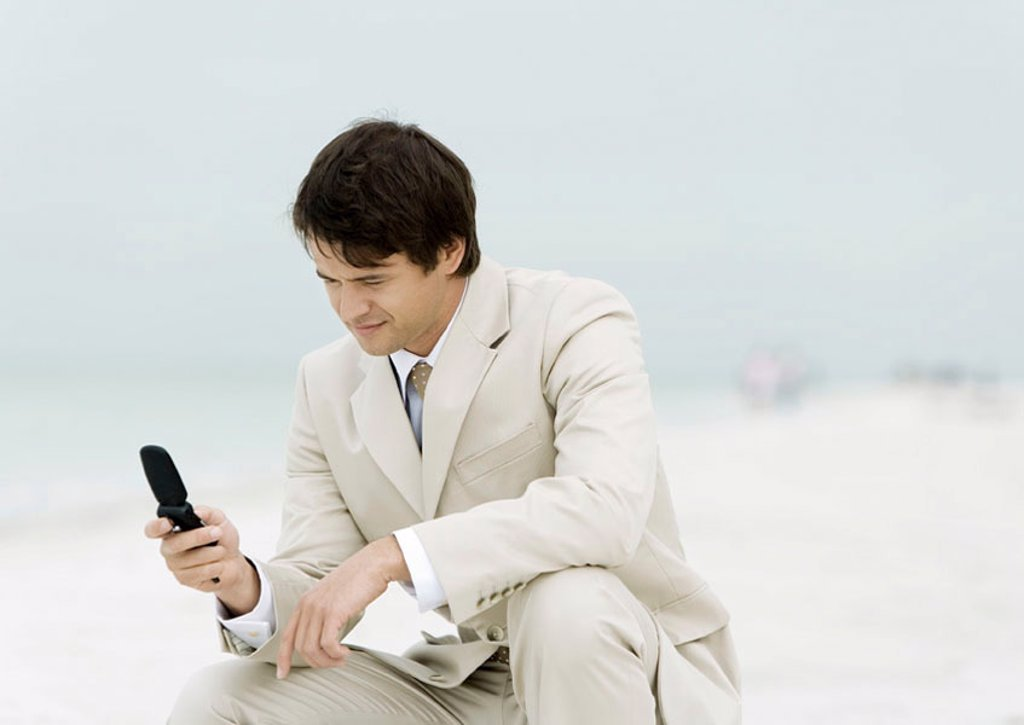 Stock Photo: 1569R-9045485 Businessman using cell phone on the beach