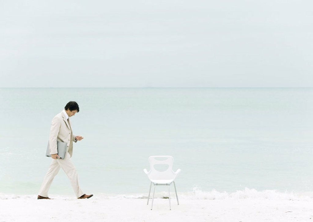 Businessman walking on beach : Stock Photo