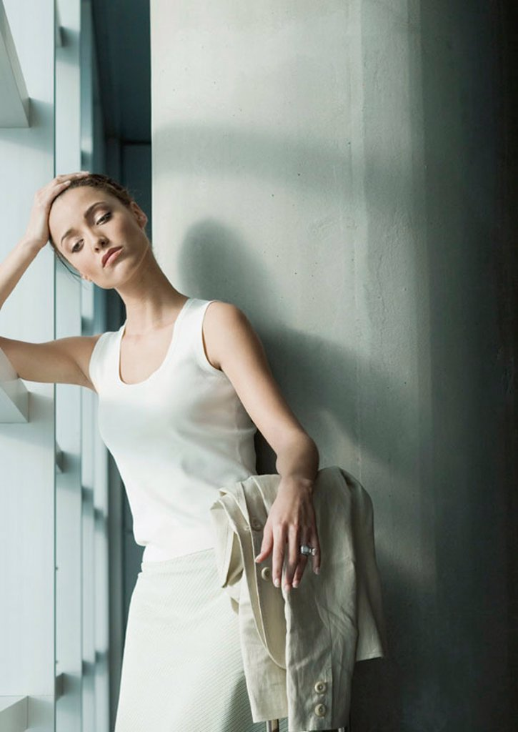 Stock Photo: 1569R-9045567 Woman standing near window, holding head