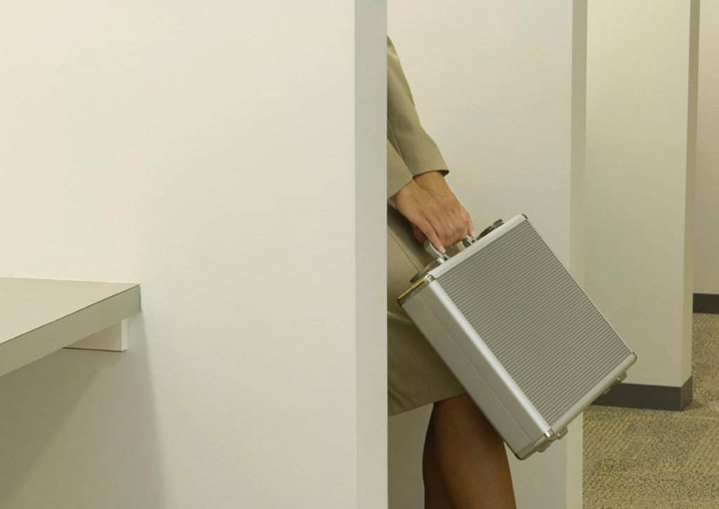 Stock Photo: 1569R-9045577 Woman behind partition, holding briefcase over knees, cropped