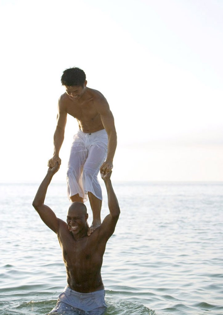 Stock Photo: 1569R-9045975 In sea, man standing on second man´s shoulders