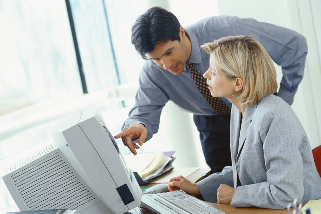 Businessman leaning over female colleague´s shoulder pointing at monitor : Stock Photo