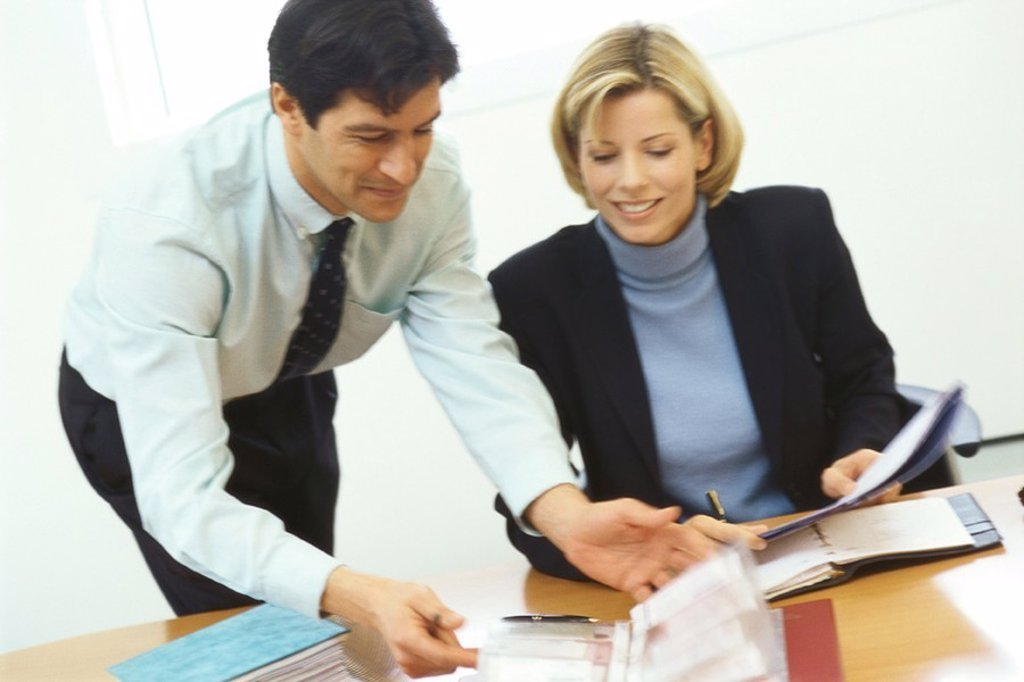 Stock Photo: 1569R-9047763 Business colleagues, man leaning over woman´s shoulder
