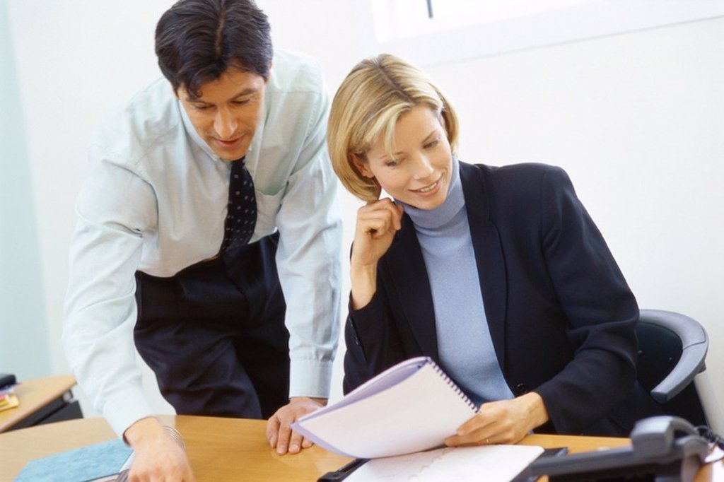 Stock Photo: 1569R-9047764 Business colleagues, man leaning over woman´s shoulder, pointing to documents