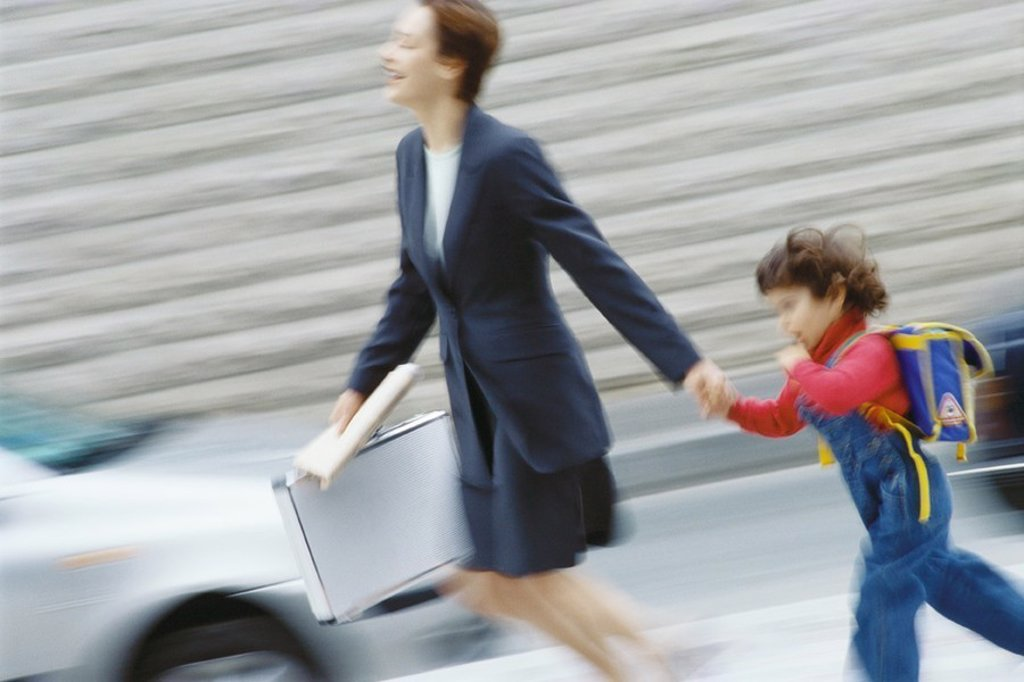 Businesswoman hurrying, holding little boy´s hand : Stock Photo