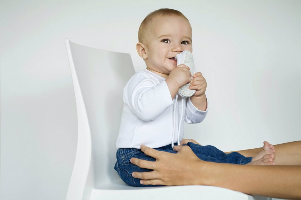 Baby sitting in chair putting shoe in mouth, mother´s arms holding baby´s legs : Stock Photo