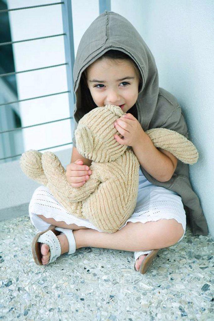 Little girl sitting on floor, whispering into teddy bear´s ear, full length : Stock Photo