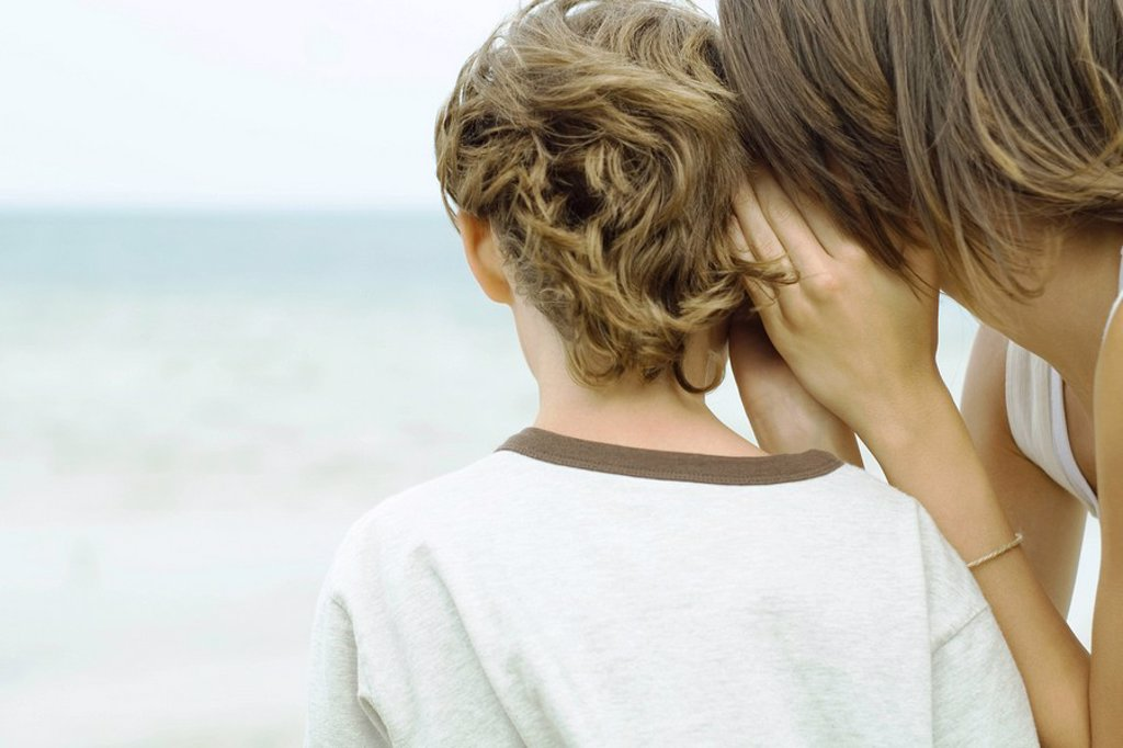 Teenage girl whispering in boy´s ear, cropped rear view : Stock Photo