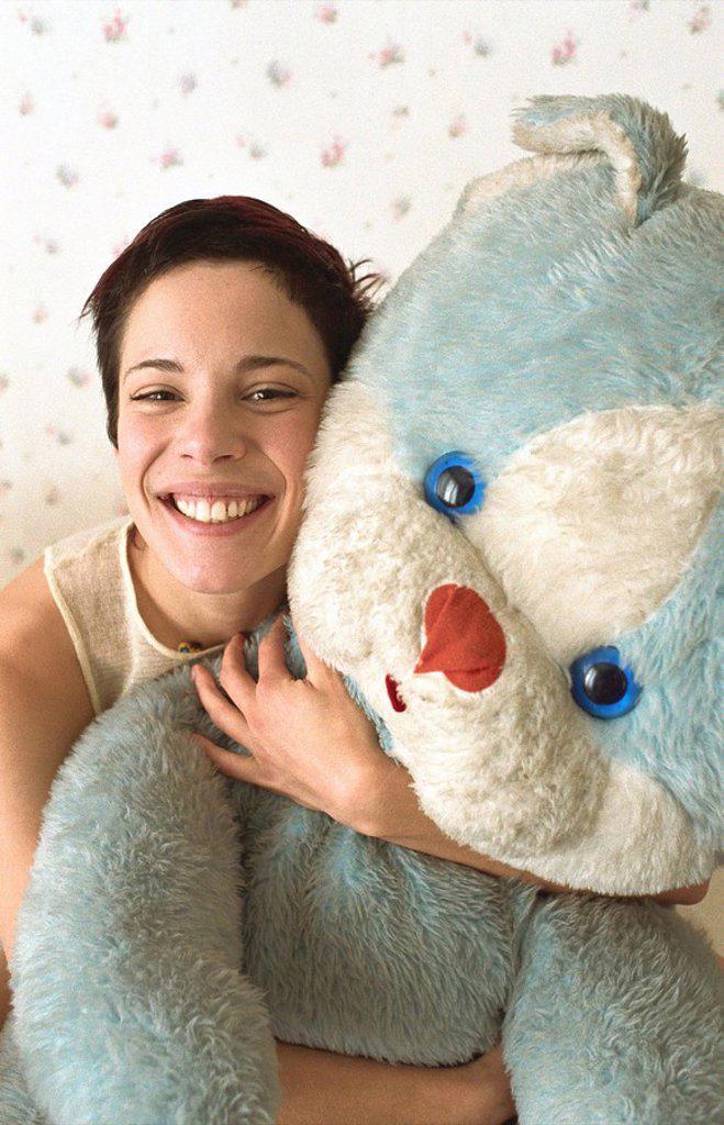 Stock Photo: 1569R-9054629 Young woman hugging teddy bear smiling at camera