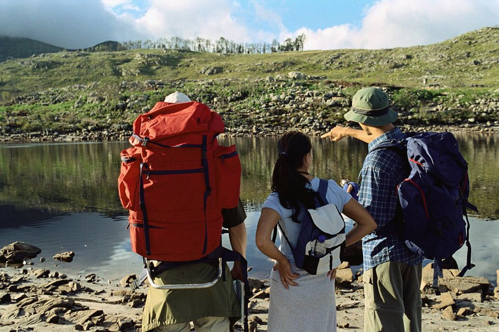Stock Photo: 1569R-9054697 Hikers deciding how to cross pond, rear view