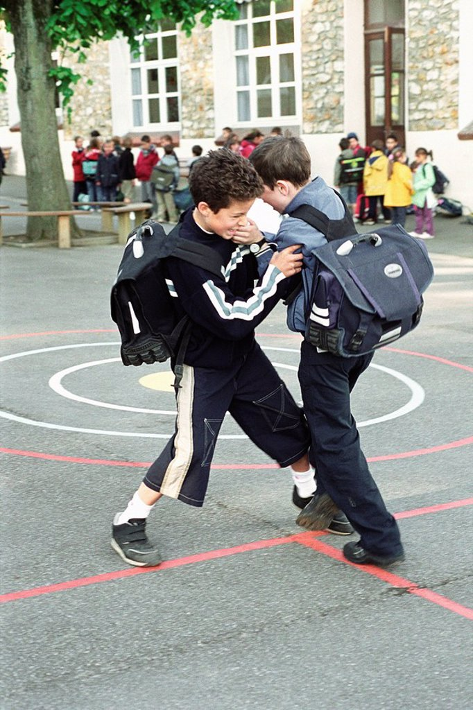 Boys fighting on school playground : Stock Photo