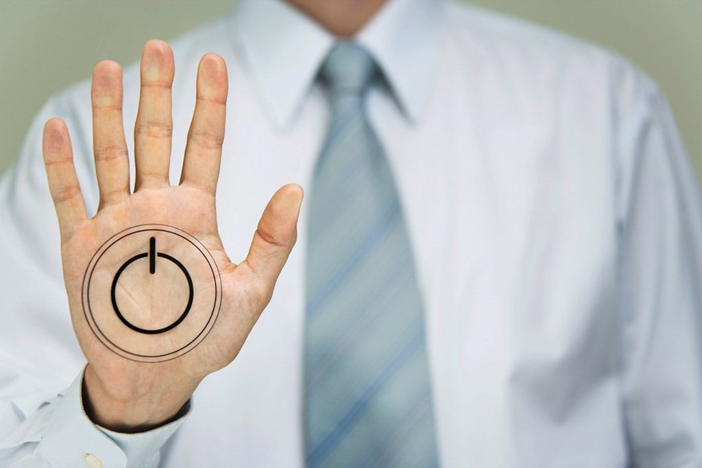 Man with power button on palm of hand : Stock Photo