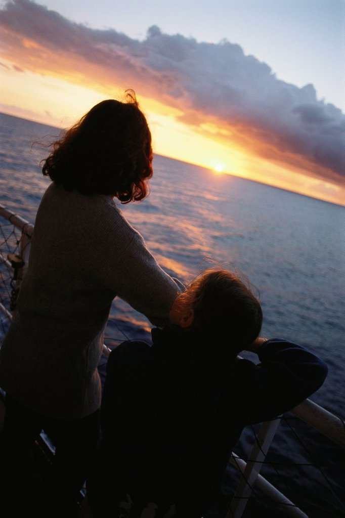 Stock Photo: 1569R-9054918 Mother and daughter on deck, looking at sunset