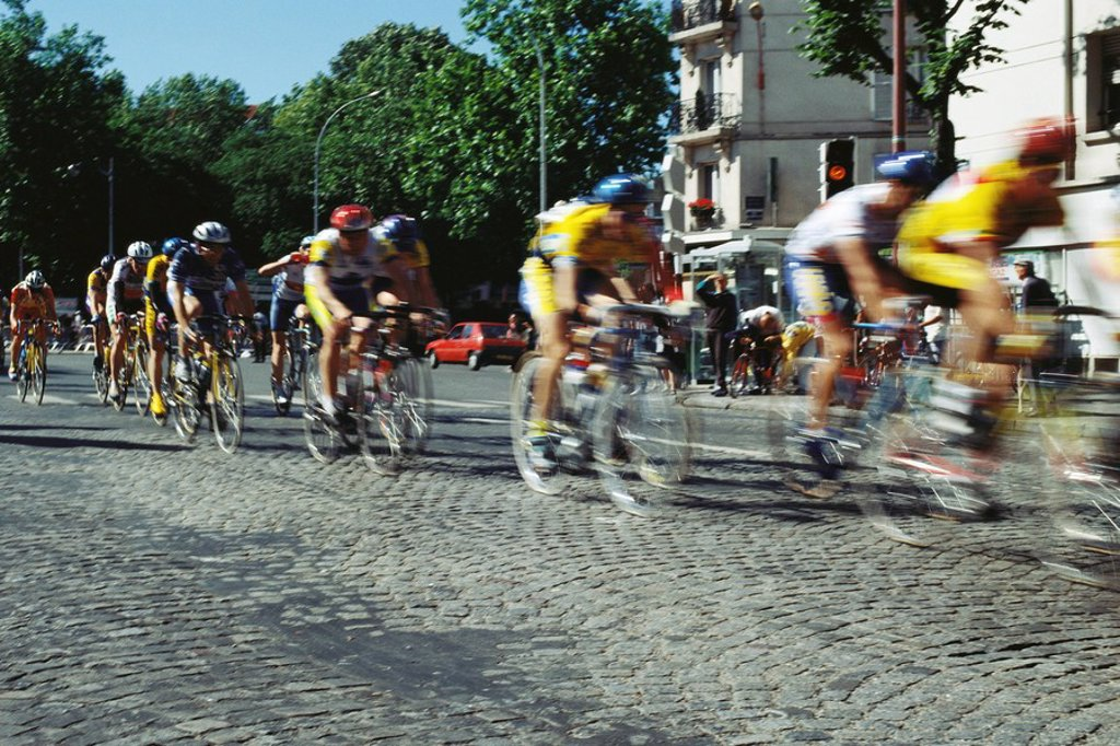 Cyclists racing on cobblestone street : Stock Photo