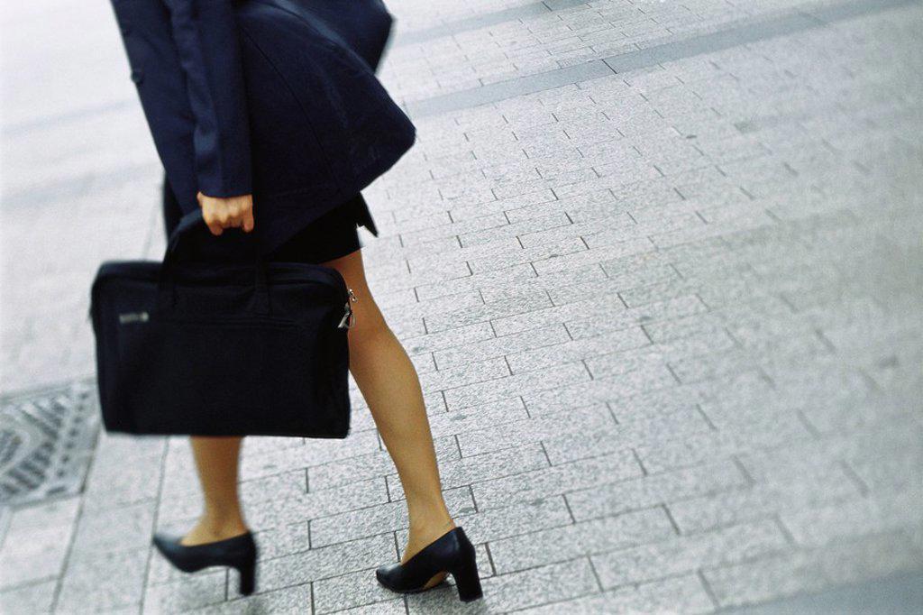 Stock Photo: 1569R-9054930 Businesswoman walking on sidewalk, cropped view