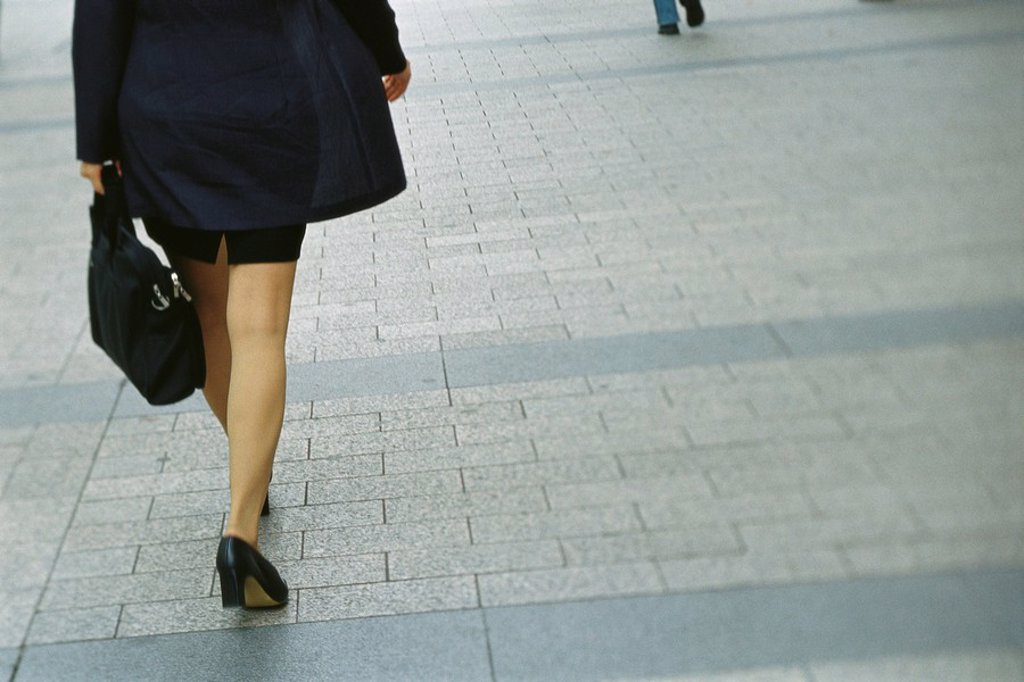 Stock Photo: 1569R-9054931 Businesswoman walking on sidewalk, rear view, cropped