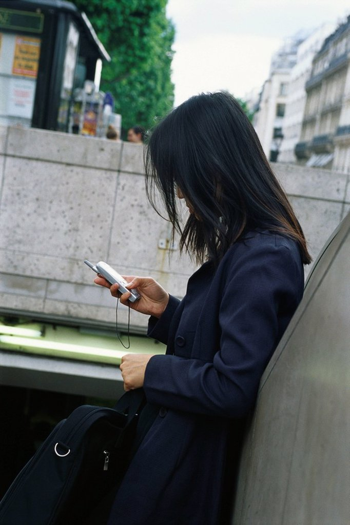 Stock Photo: 1569R-9054939 Businesswoman leaning against wall, looking at cell phone