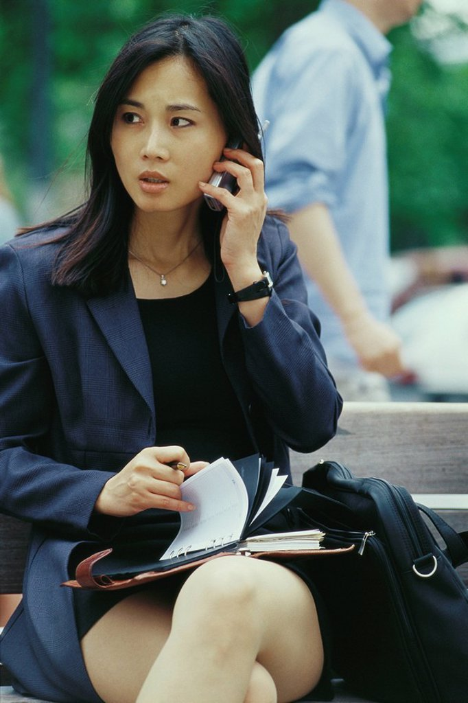 Businesswoman sitting on bench, using cell phone and flipping through agenda : Stock Photo