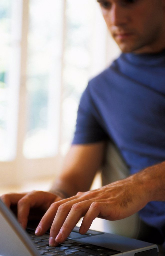 Man typing on laptop, focus on hands : Stock Photo