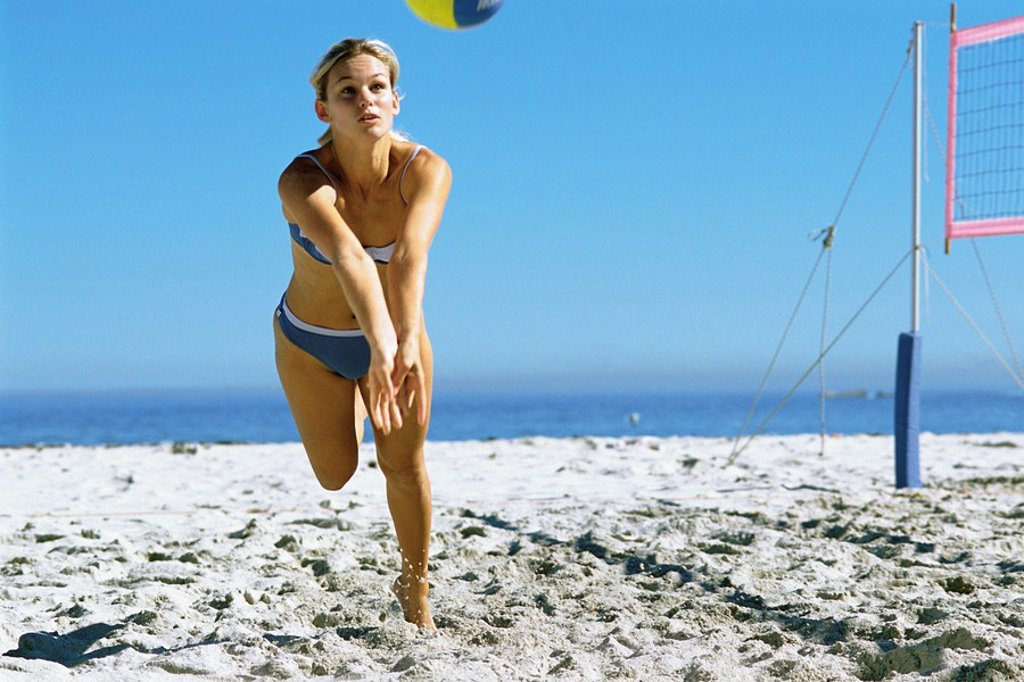 Female playing beach volleyball running to catch ball : Stock Photo