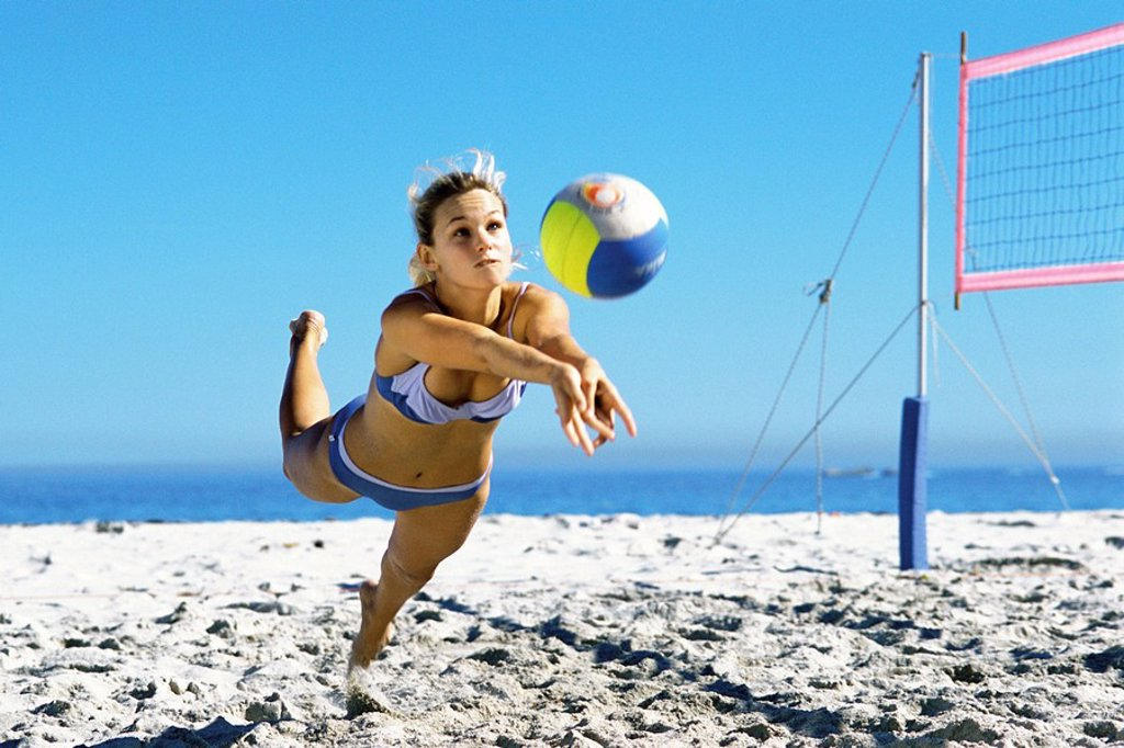 Stock Photo: 1569R-9055287 Female playing beach volleyball diving to catch ball