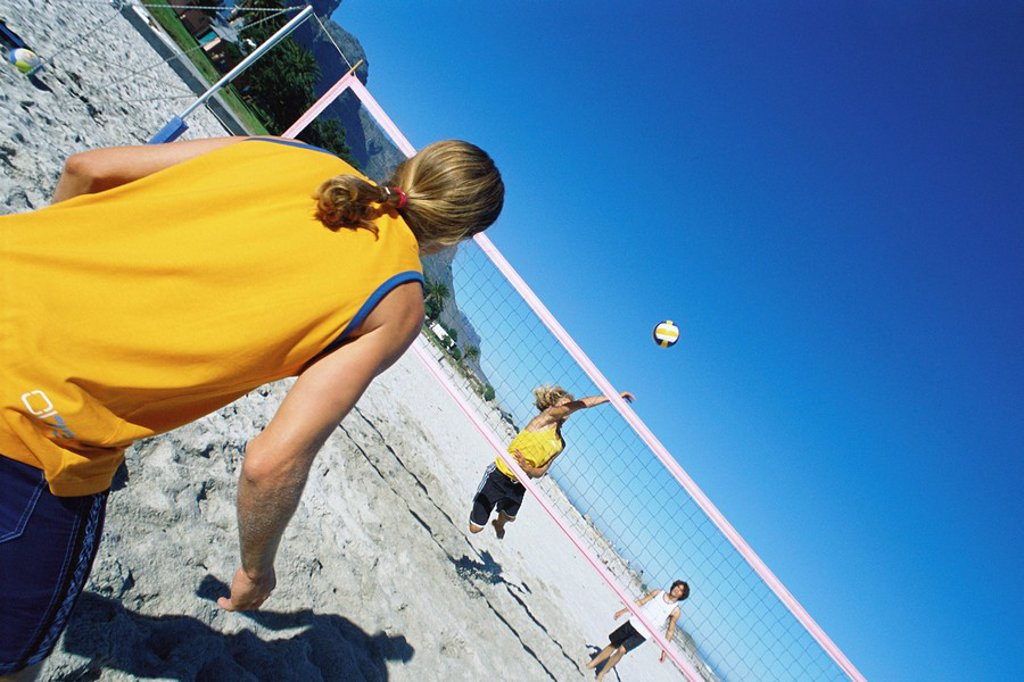 Stock Photo: 1569R-9055288 Friends playing beach volleyball
