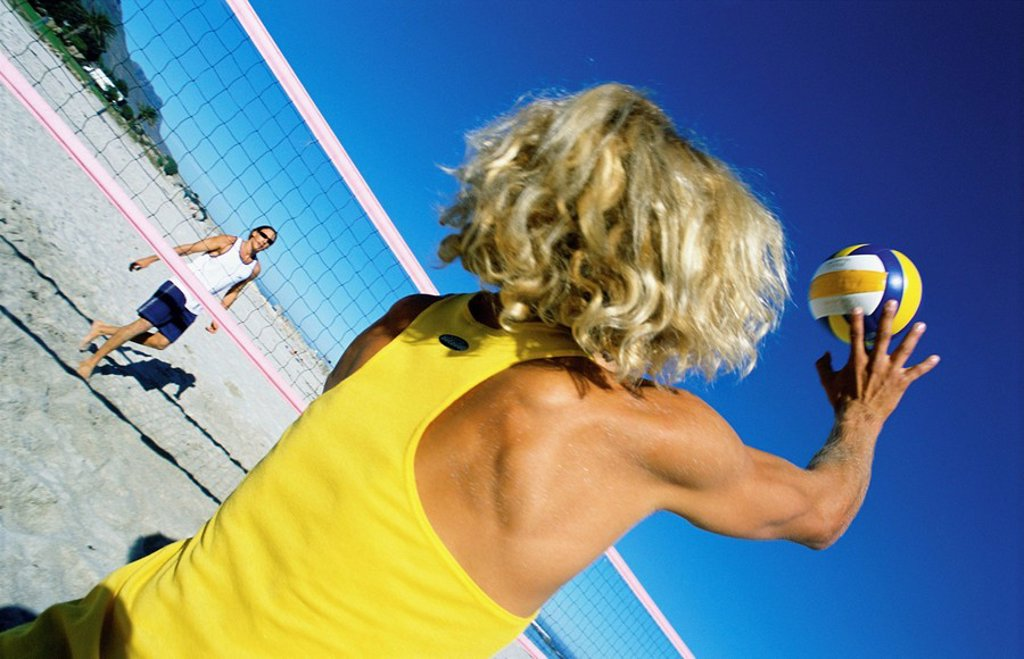 Male playing beach volleball preparing to hit ball : Stock Photo