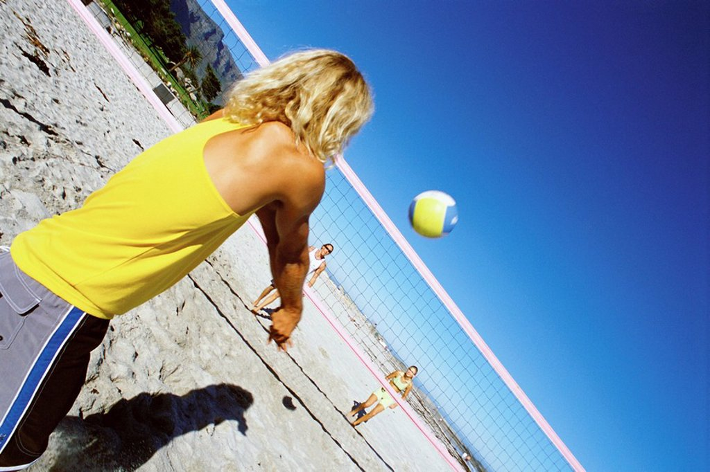 Male volleying beachball over net : Stock Photo