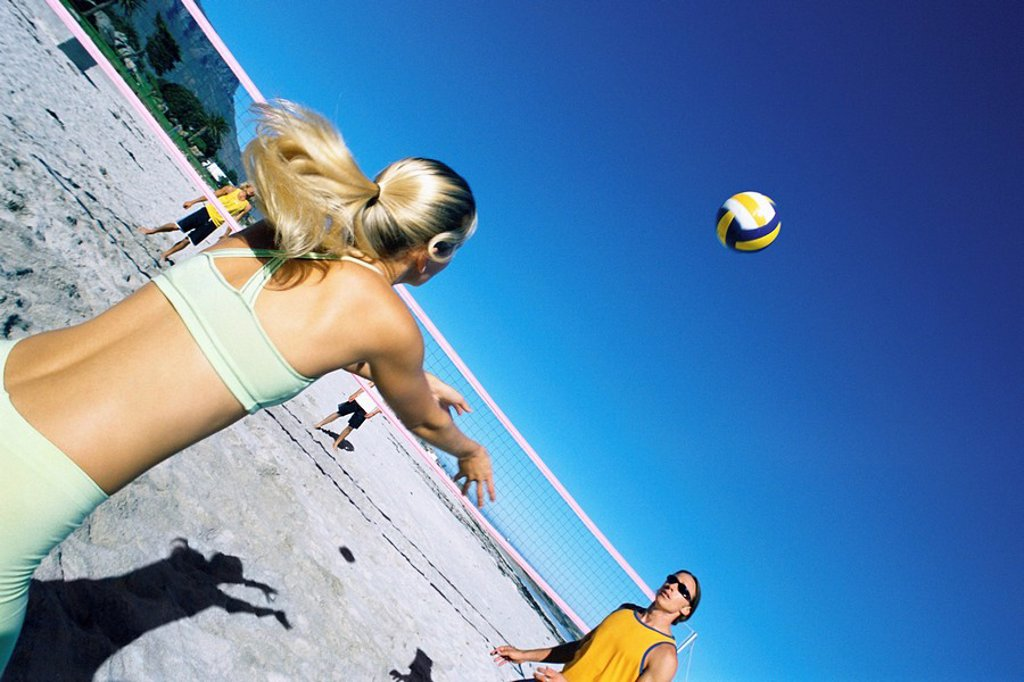 Female preparing to volley ball to teammate : Stock Photo