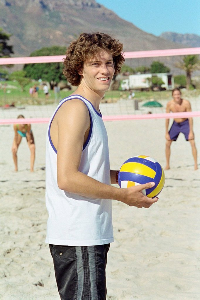 Male holding volleball, playing beach volleyball : Stock Photo
