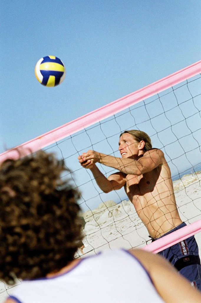 Male playing beach volleball, preparing to hit ball : Stock Photo
