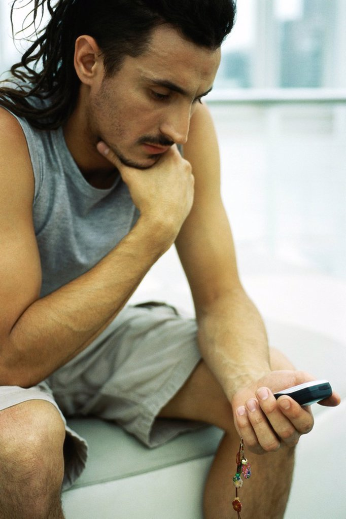 Man sitting with hand under chin, looking at cell phone : Stock Photo