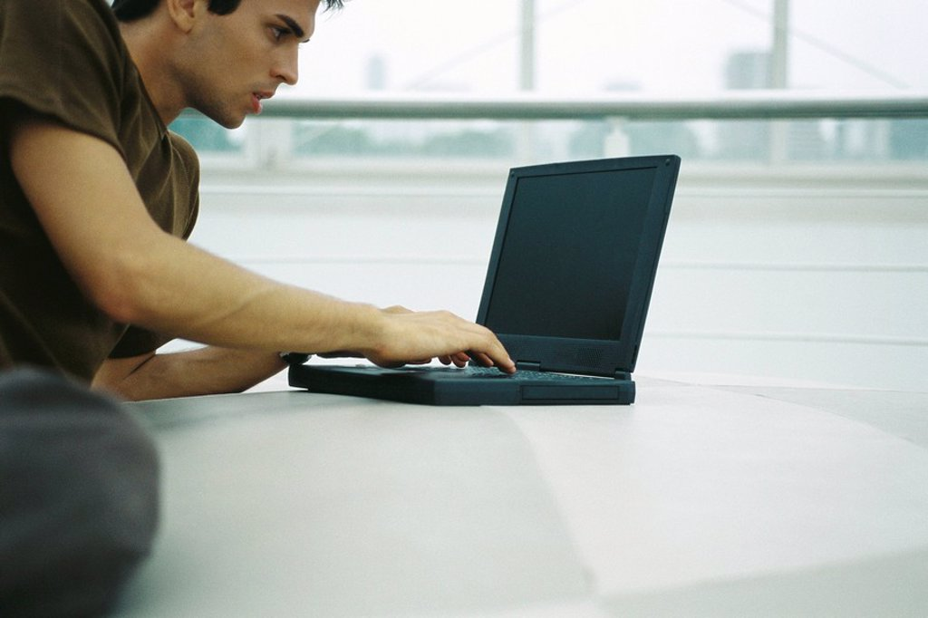 Stock Photo: 1569R-9055387 Man reclining on floor using laptop computer