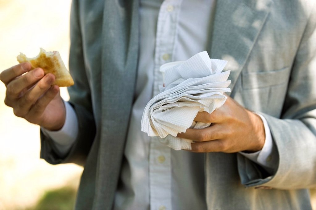 Person holding half eaten pastry in one hand and disposable cup and paper napkins in other hand : Stock Photo