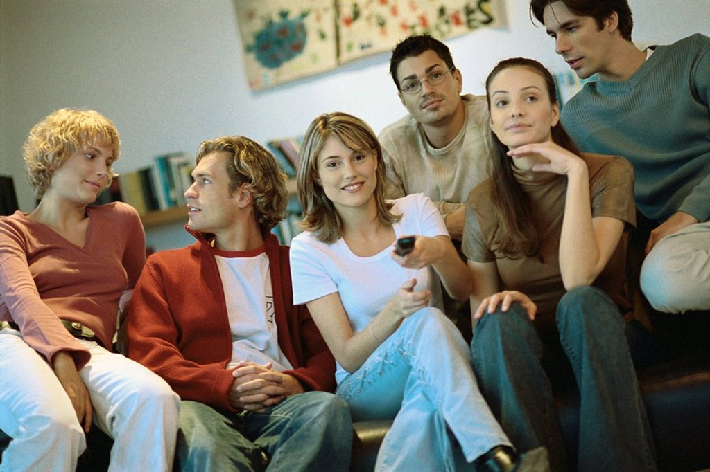 Group of friends sitting close together on sofa watching TV : Stock Photo