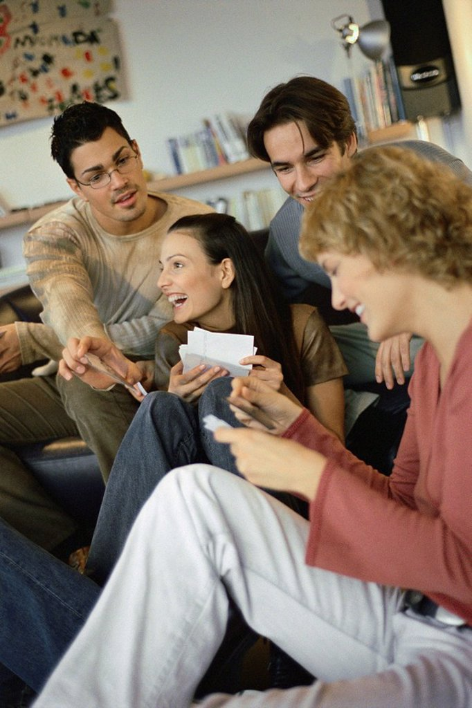 Stock Photo: 1569R-9055449 Friends sitting together sharing photos with one another