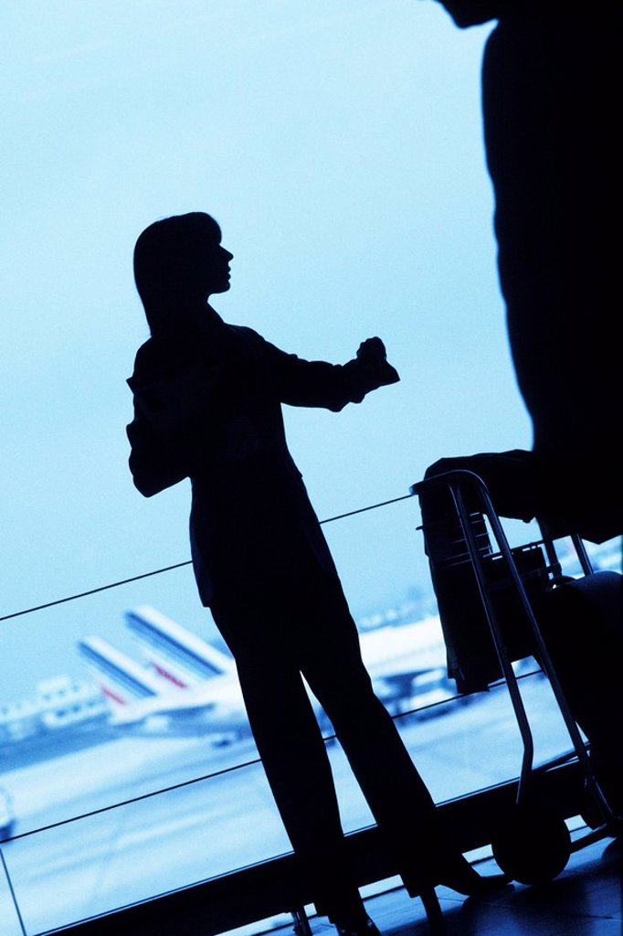 Silhouette of woman traveler standing with luggage cart looking away in airport : Stock Photo