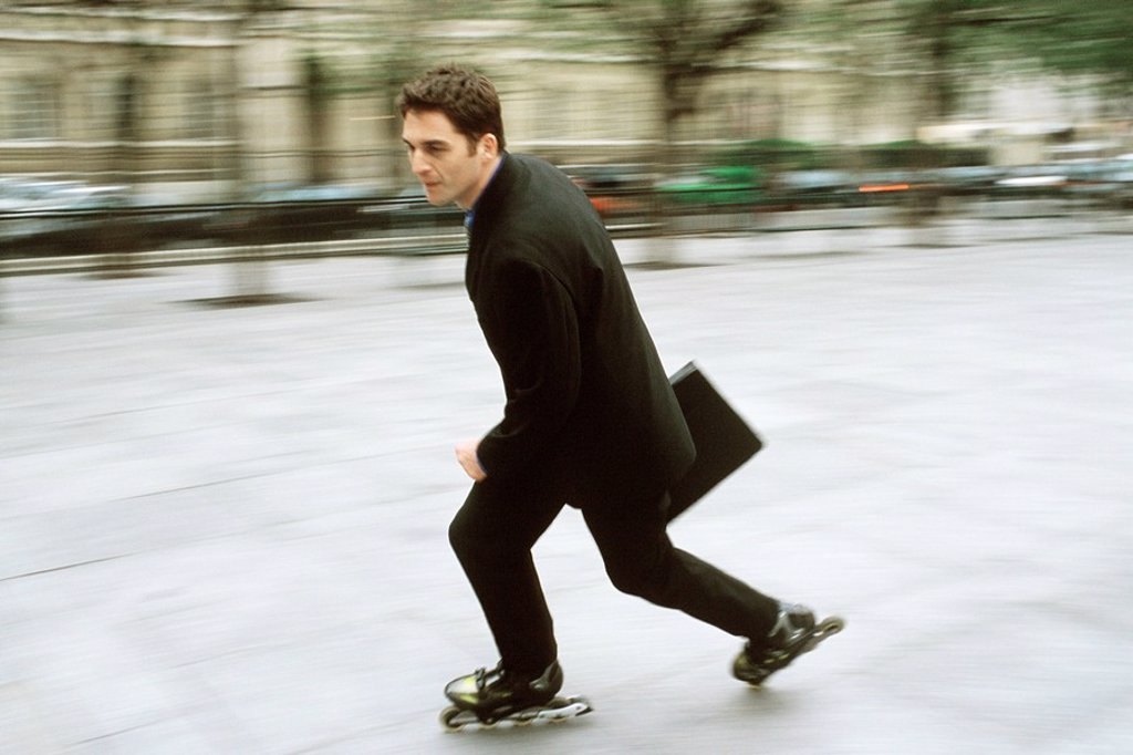 Man in business attire inline skating carrying briefcase in city square : Stock Photo