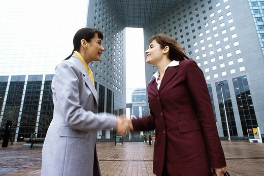 Businesswomen shaking hands, meeting in plaza outside office building : Stock Photo