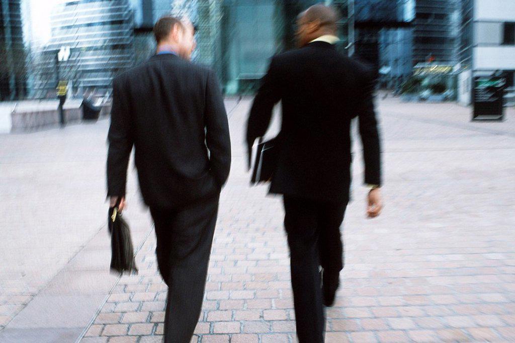 Businessmen walking together along city sidewalk : Stock Photo