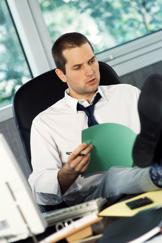Man with feet up on office desk reviewing document : Stock Photo